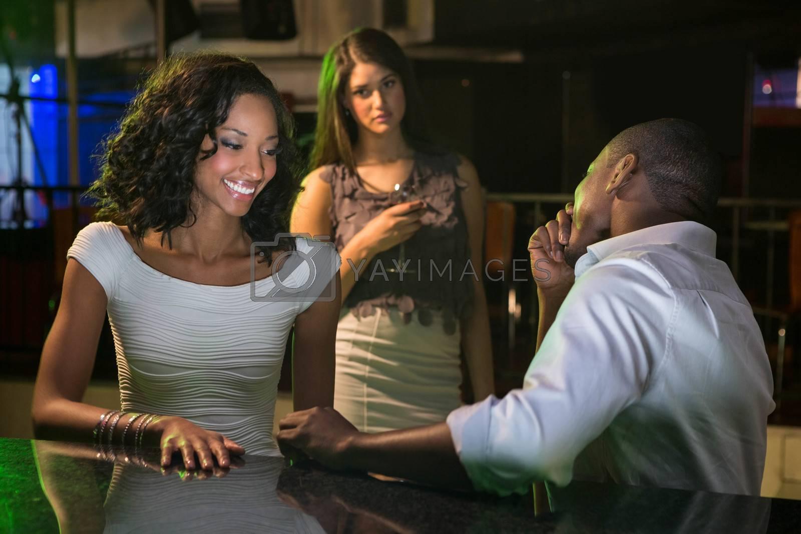 Unhappy woman looking at a couple flirting near bar counter in bar