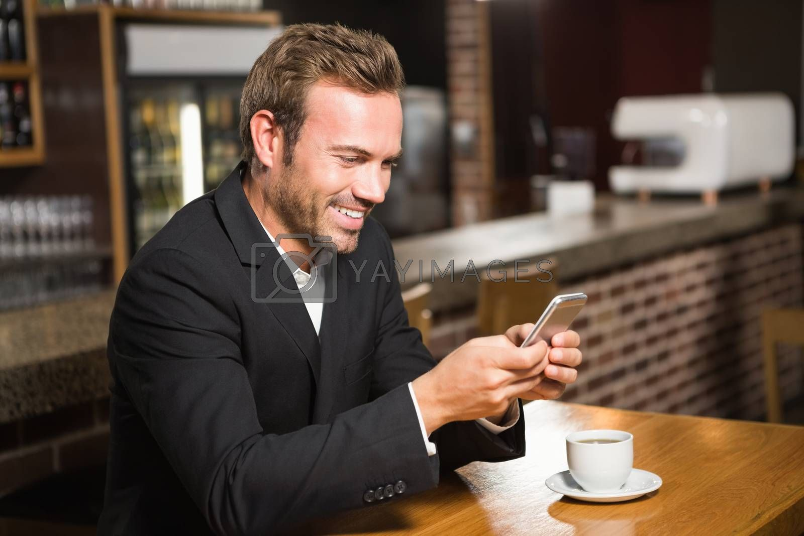 Handsome man looking at smartphone and having a coffee in a pub