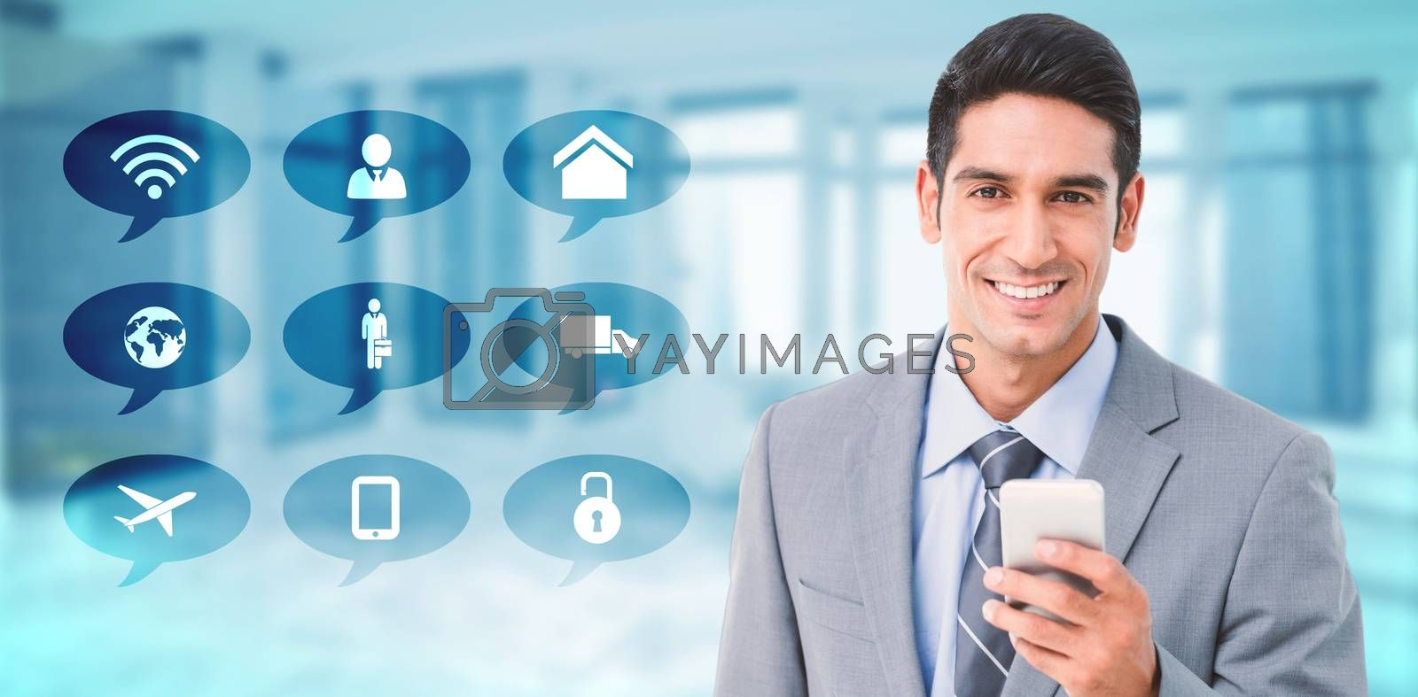 Businessman using mobile phone with colleagues behind against modern room overlooking city