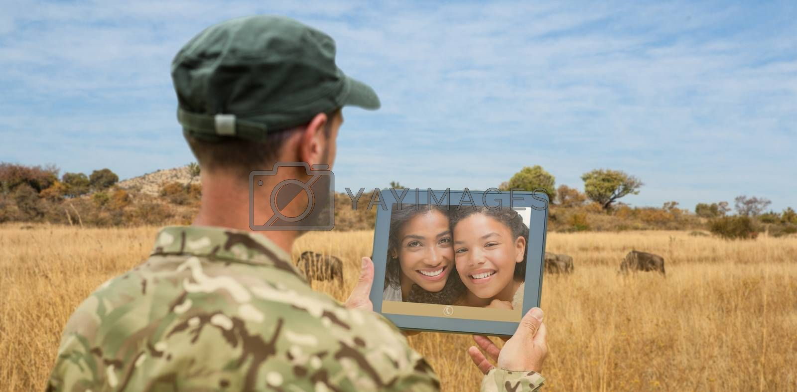 Soldier using tablet pc against landscape with animals