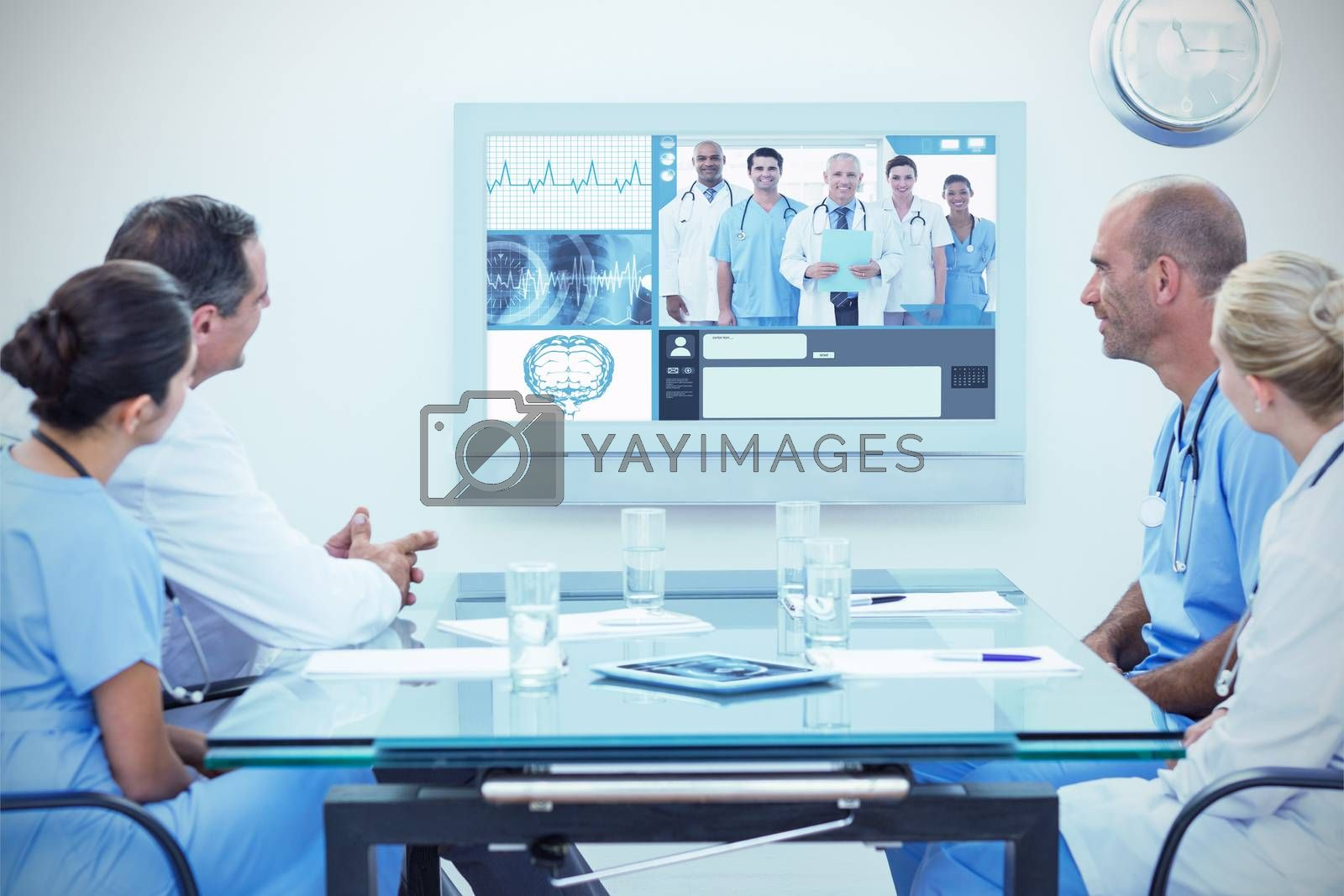 Team of doctors having a meeting against team of smiling doctors looking at camera