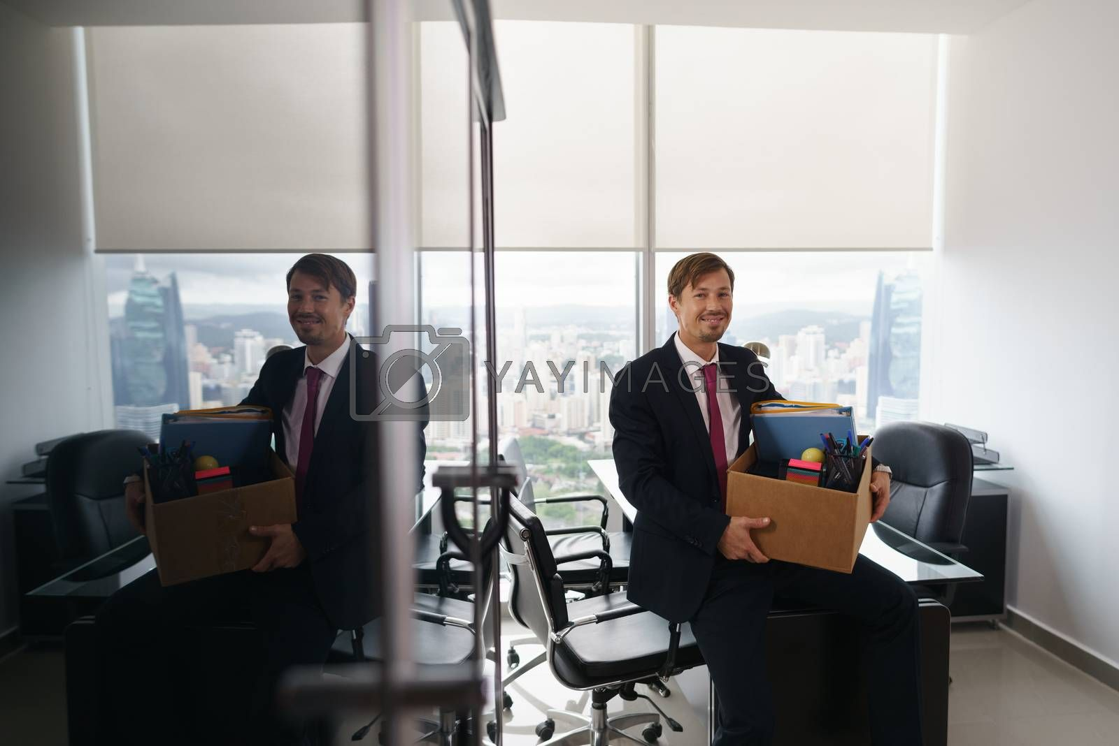 Businessman recently hired for corporate job moves into his new executive office with a view of the city. He leans on desk and smiles at camera happy.