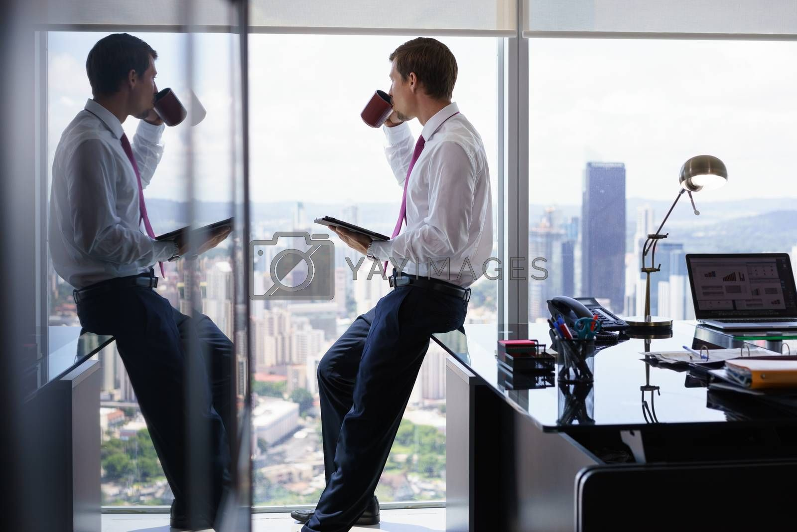 Adult businessman sitting on desk in modern office and reading news on tablet pc with a cup of coffee. The man looks out of the window and contemplates the city and skyscrapers.