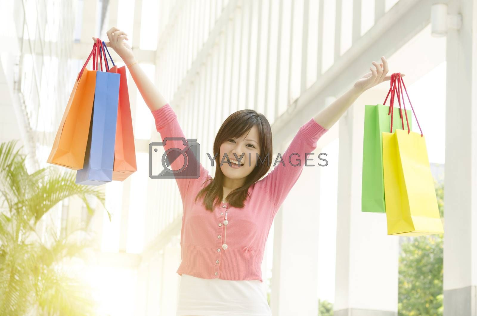 Cheerful young Asian girl with shopping bags walking out the mall. Beautiful golden sunlight at background.
