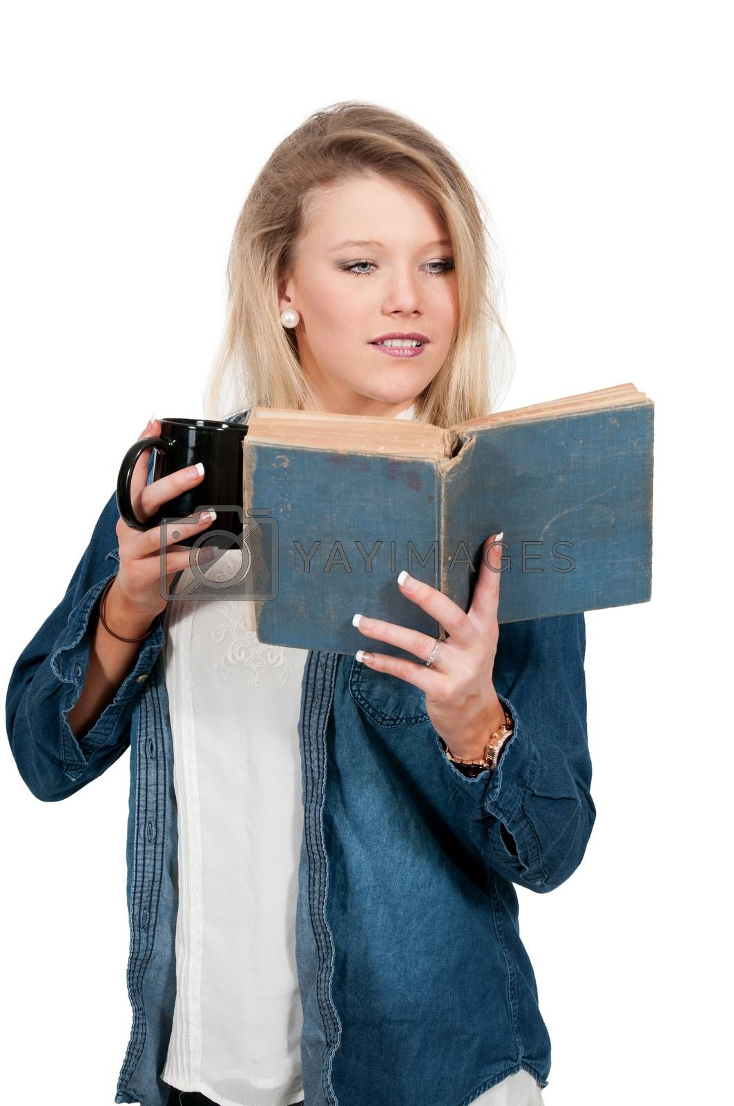 Beautiful woman reading a book while drinking a hot beverage