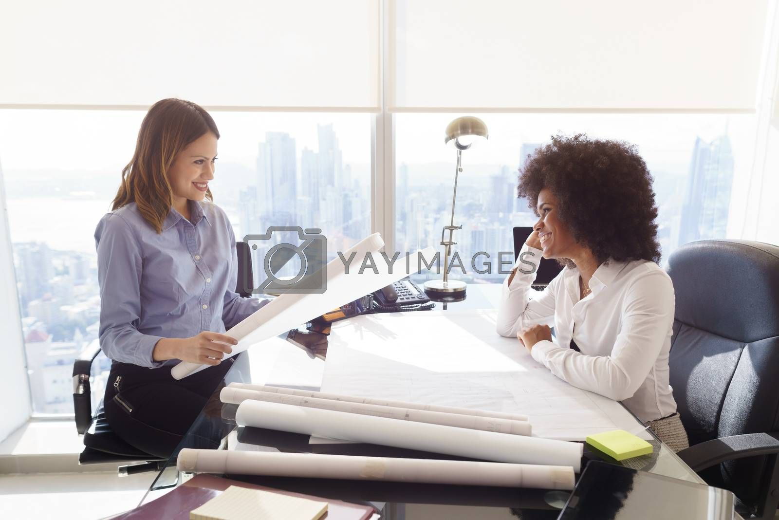 Team of two female architects, sitting at desk in office. The women talk and smile reviewing a building plan. Medium shot