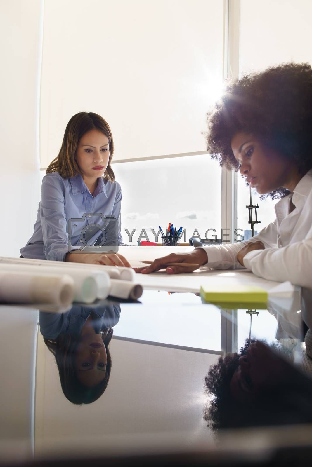 Team of two female architects, sitting at desk in office. The women talk reviewing a building plan. Reflections on table and copy space