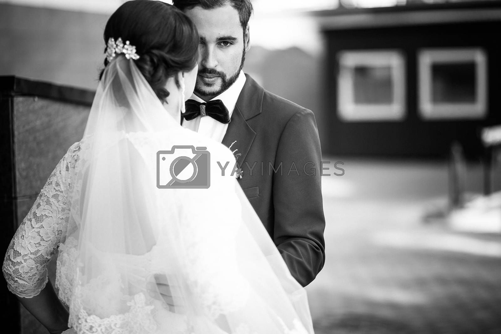 The bride and groom black and white portrait. The man has a serious look, wedding retro classic.