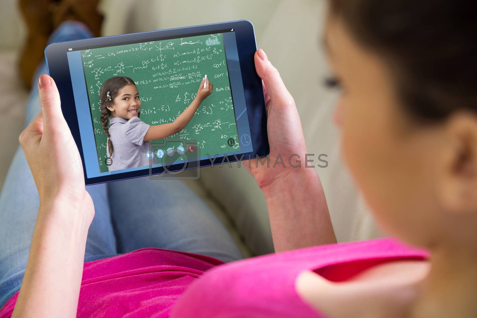 Woman using tablet at home against green