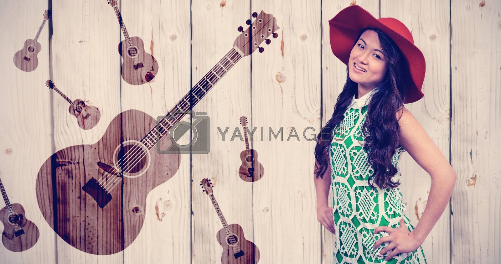 Asian woman with hat posing for camera against wooden background