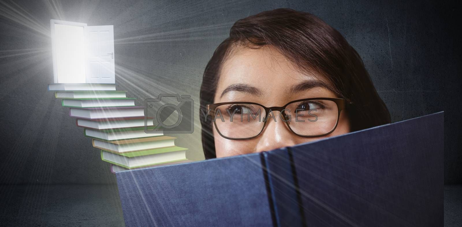 Pretty student hiding face behind a book against steps made from books leading to door in grey room