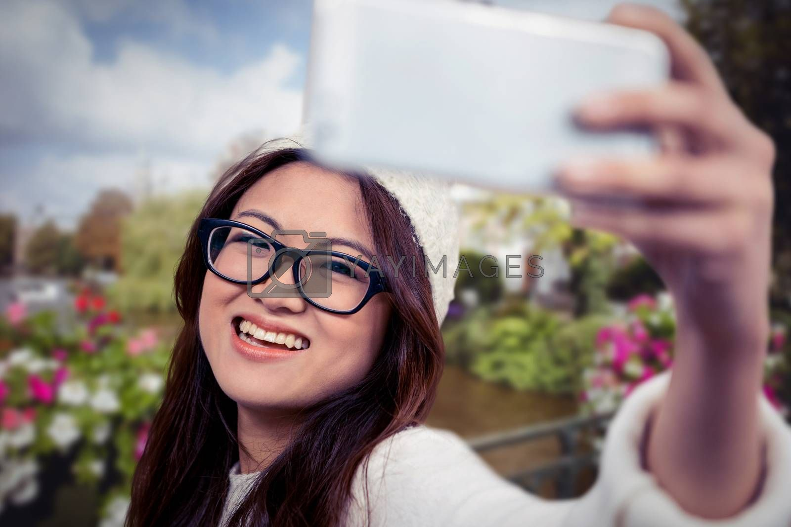 Smiling Asian woman taking selfie against canal in amsterdam