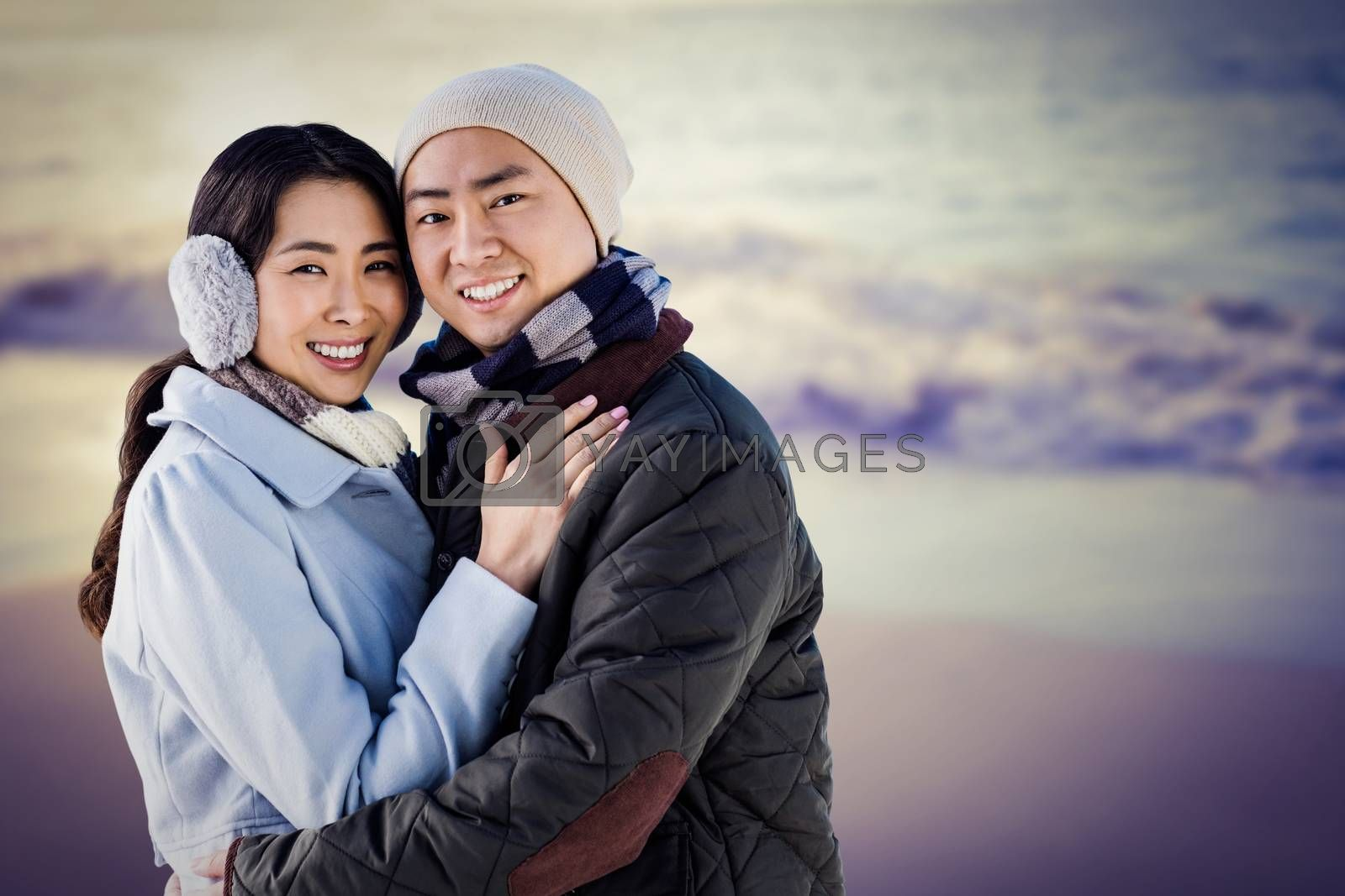 Portrait of couple embracing against beautiful beach on a sunny day