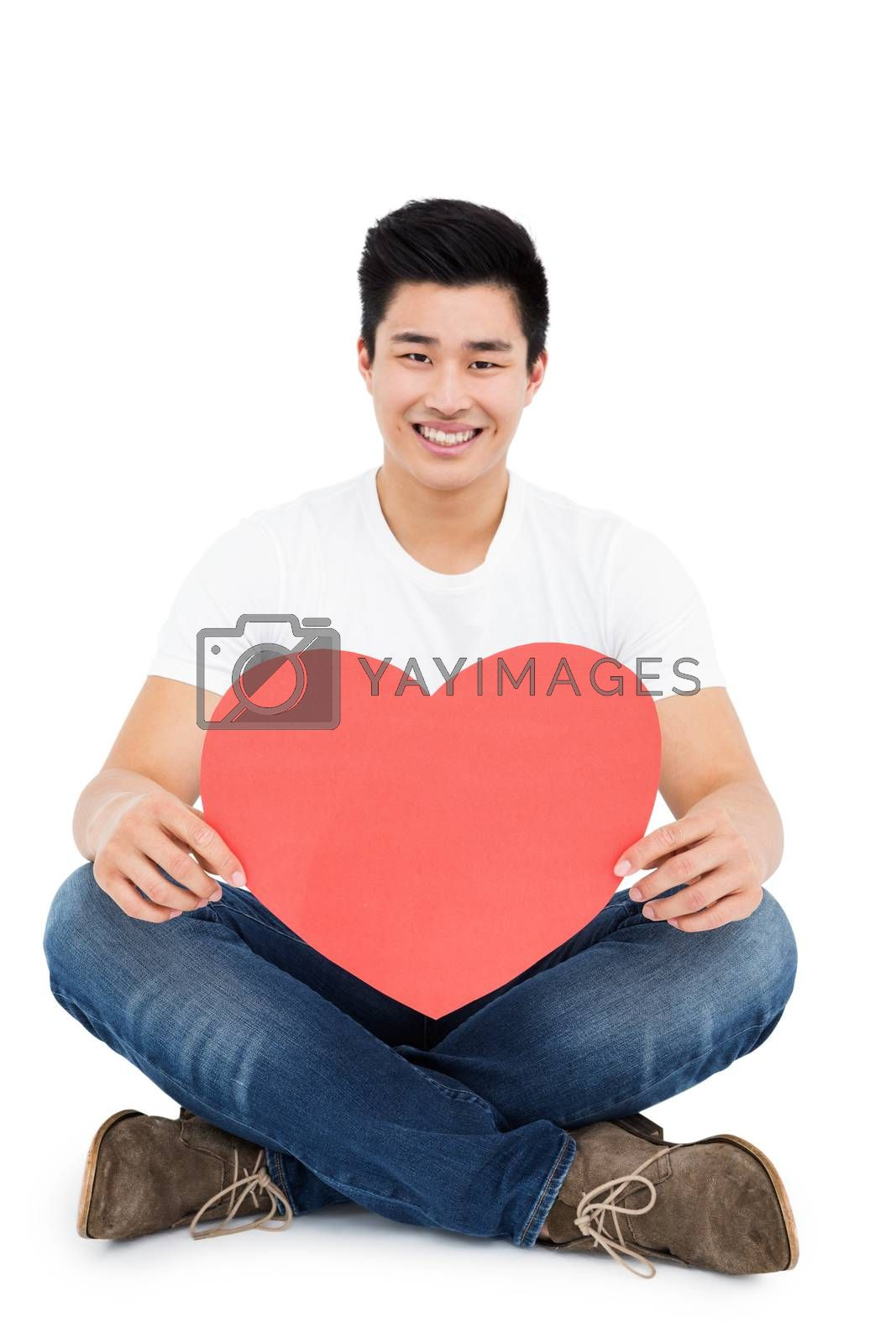 Young man holding heart shape on white background