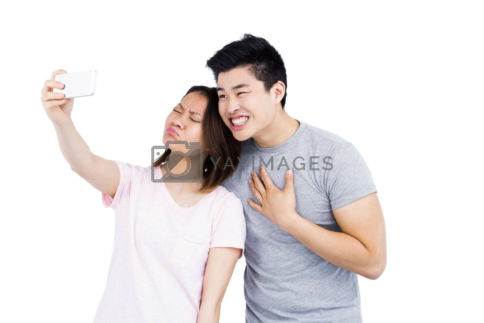 Young couple taking a selfie on smartphone on white background