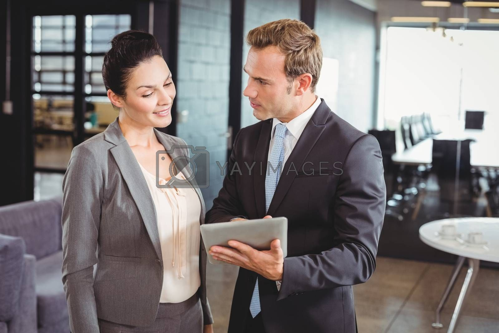 Businessman and businesswoman using digital tablet in office