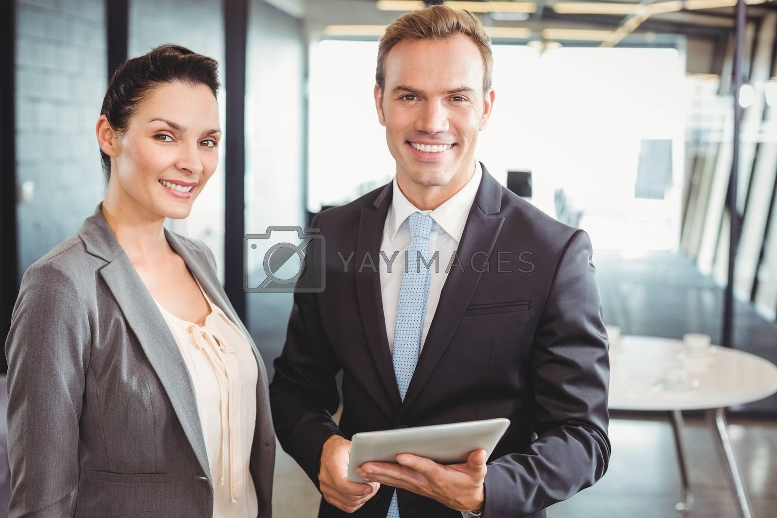 Portrait of businessman and businesswoman holding digital tablet at office