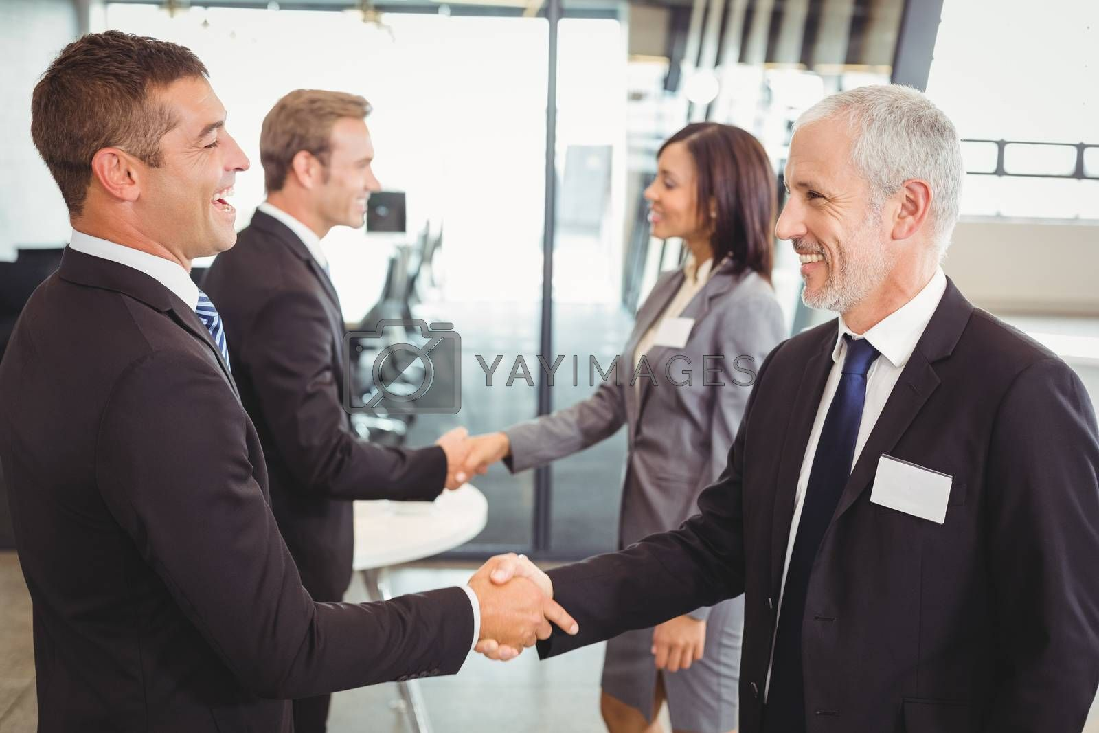Businesspeople shaking hands with each other in the office