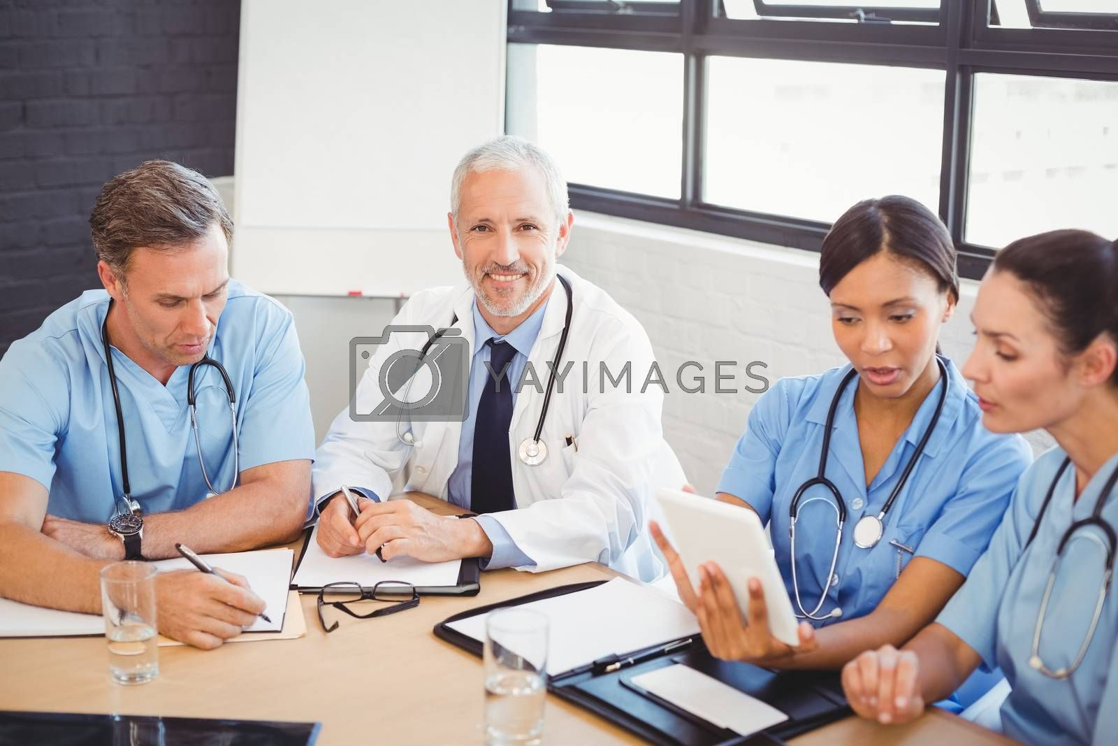 Portrait of male doctor smiling in conference room and colleagues discussing beside him