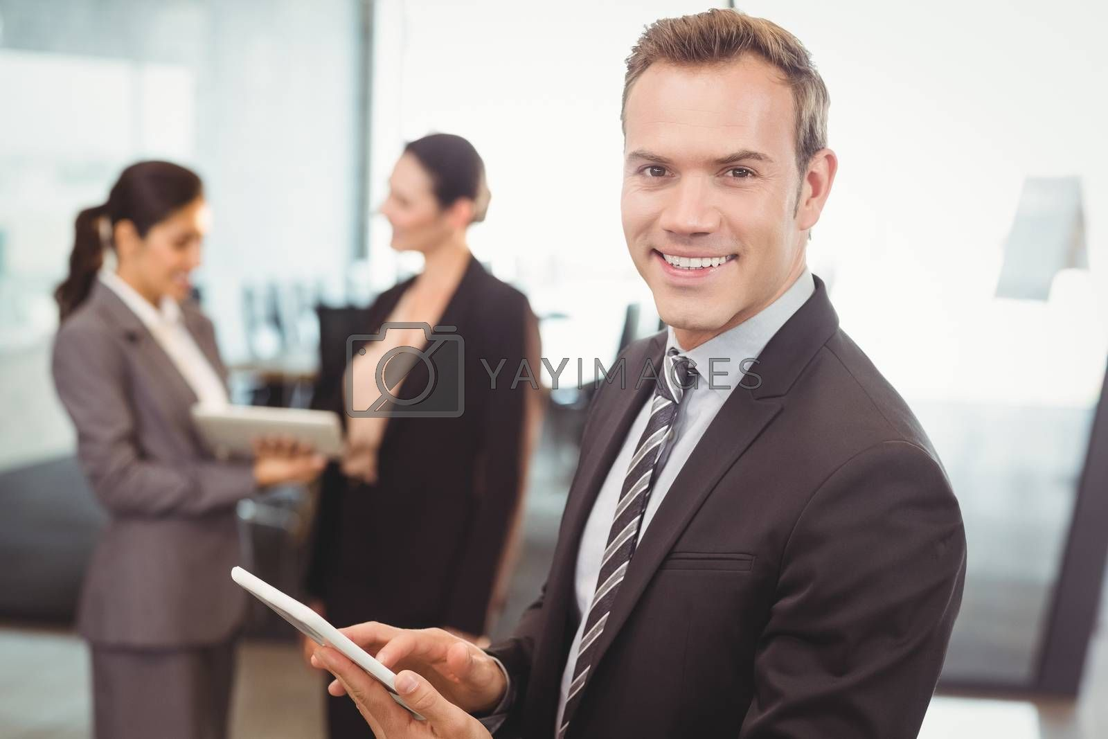 Portrait of businessman using digital tablet in office