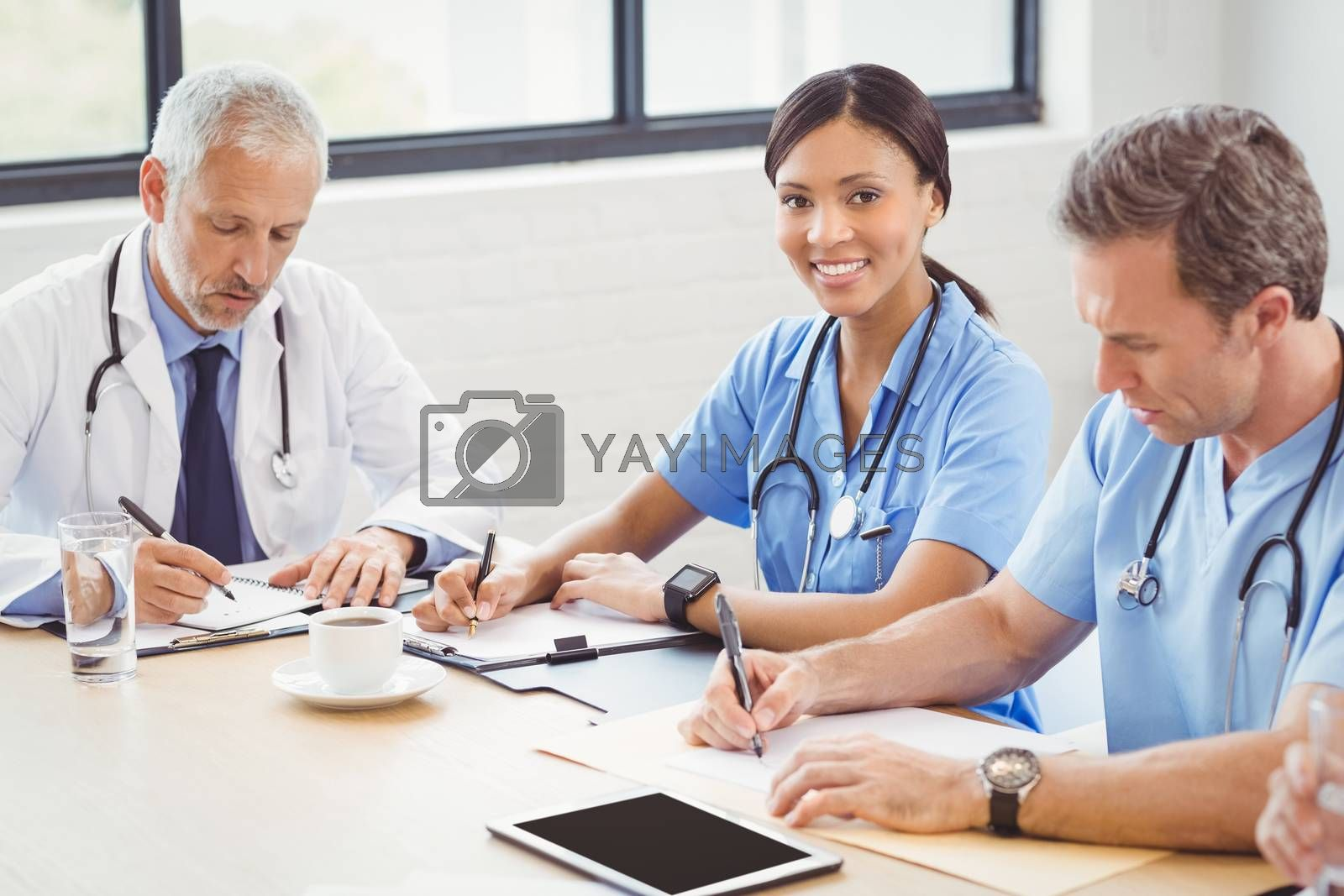 Medical team sitting and writing a report in conference room in hospital