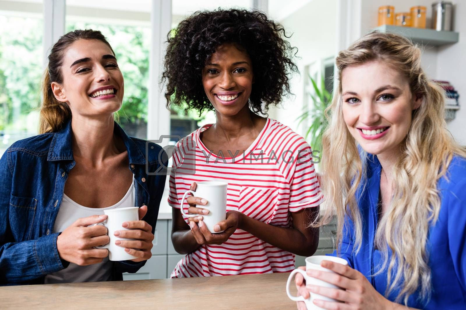 Portrait of cheerful female friends drinking coffee at table in house
