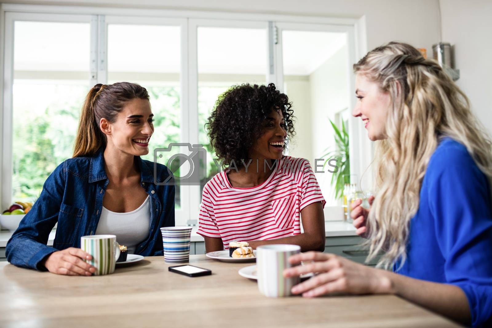 Young female friends smiling while having breakfast at table in house