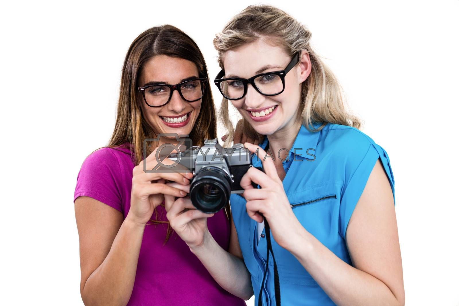 Portrait of smiling friends holding digital camera on white background