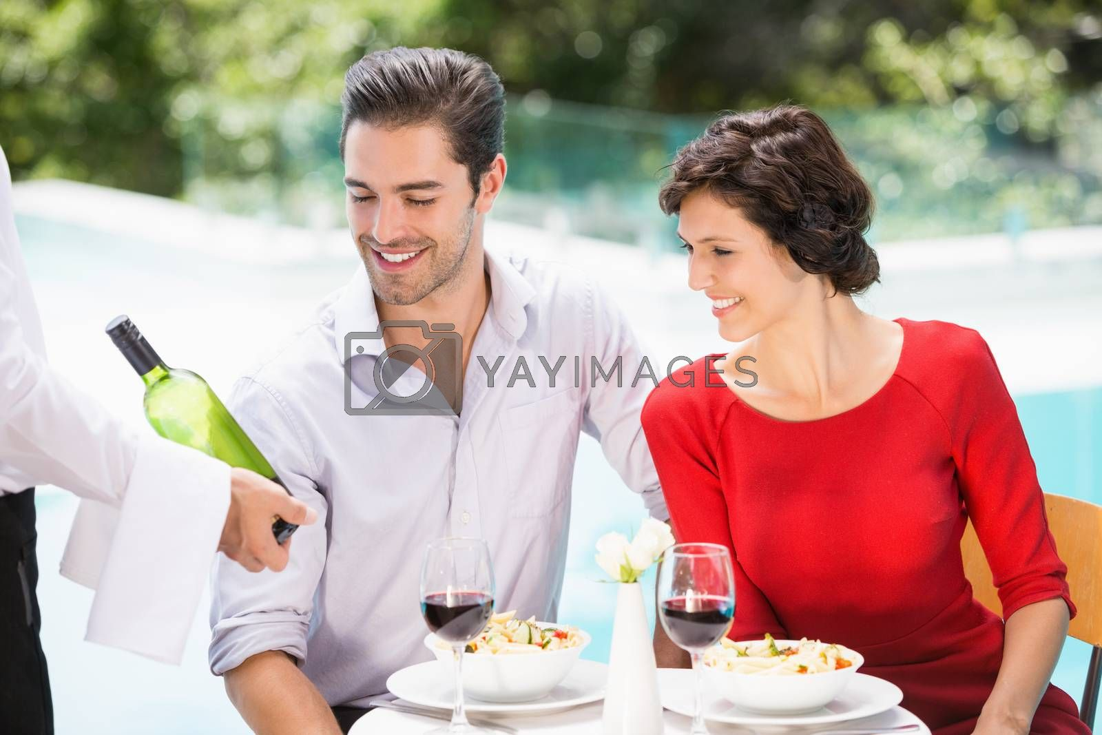 Waiter showing wine bottle to couple at poolside