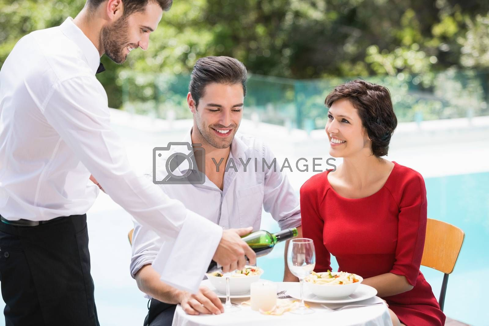 Smiling waiter serving red wine to couple at poolside