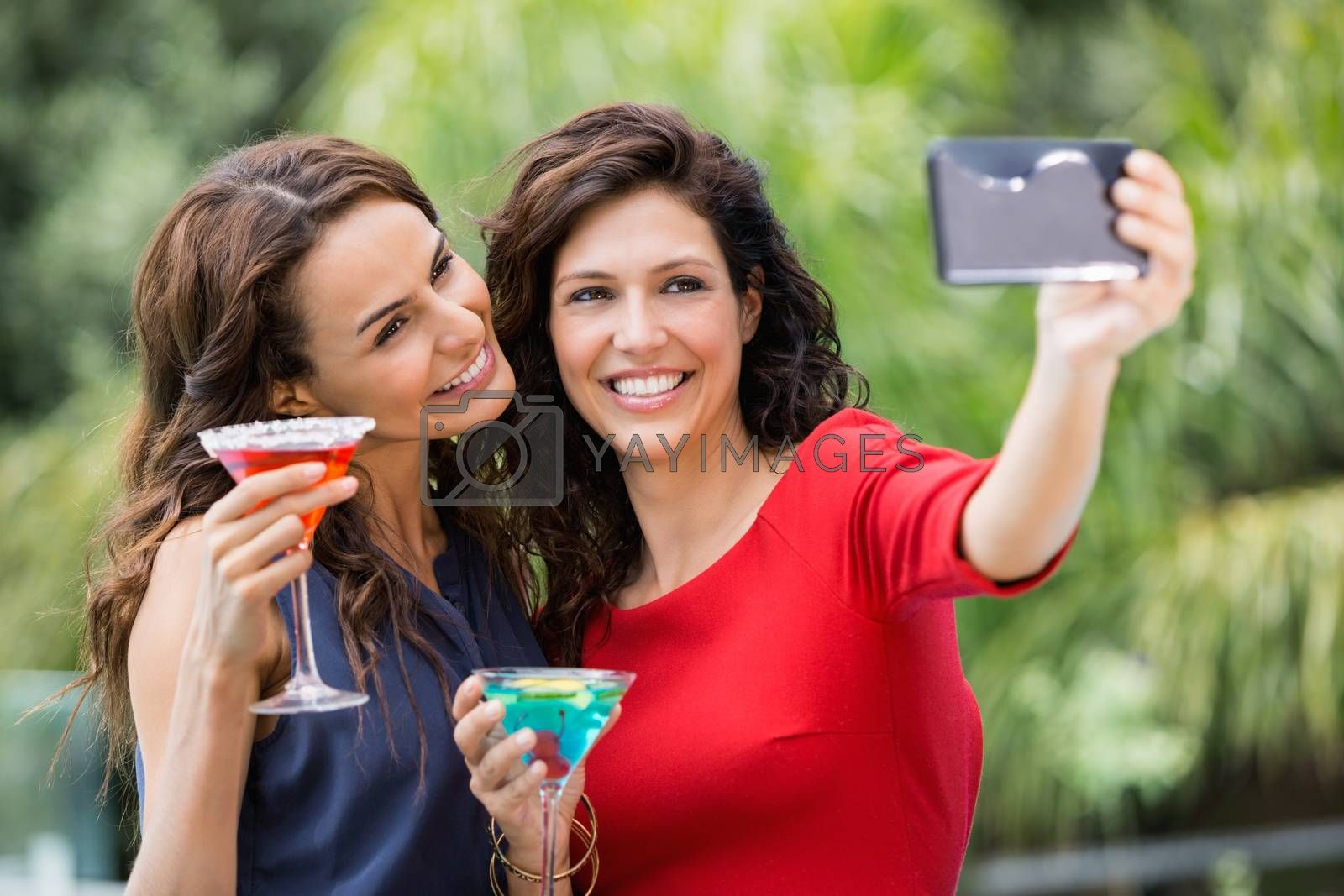 Smiling friends taking self portrait while holding drinks at resort