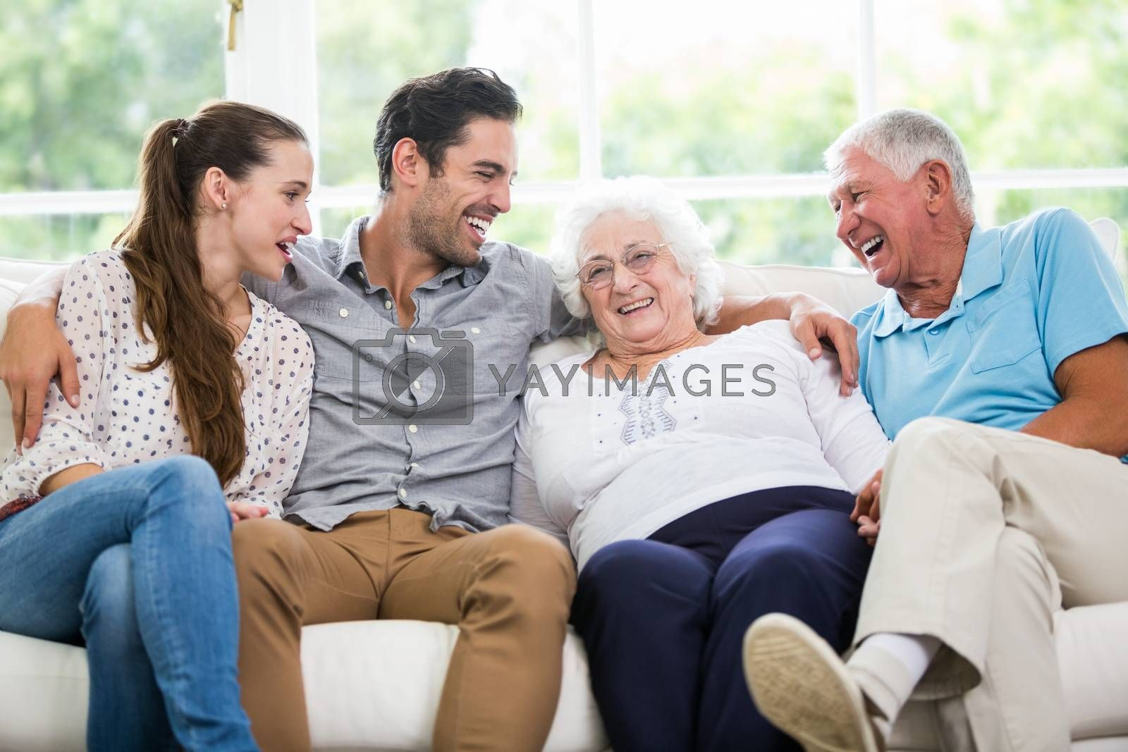 Smiling family discussing while sitting on sofa at home