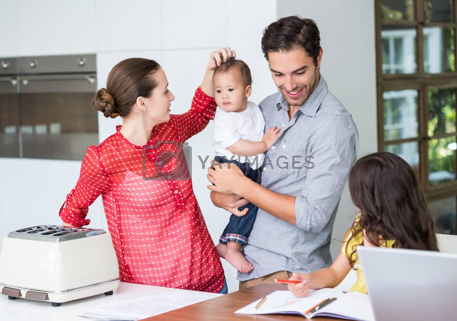 Happy family at desk  by Wavebreakmedia