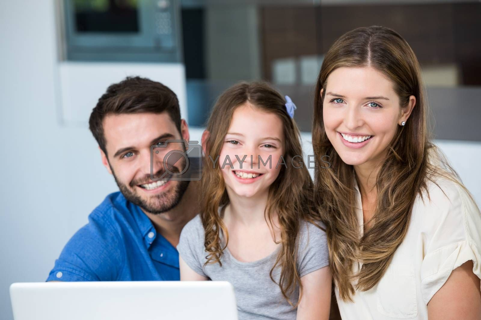 Portrait of smiling family with laptop at home