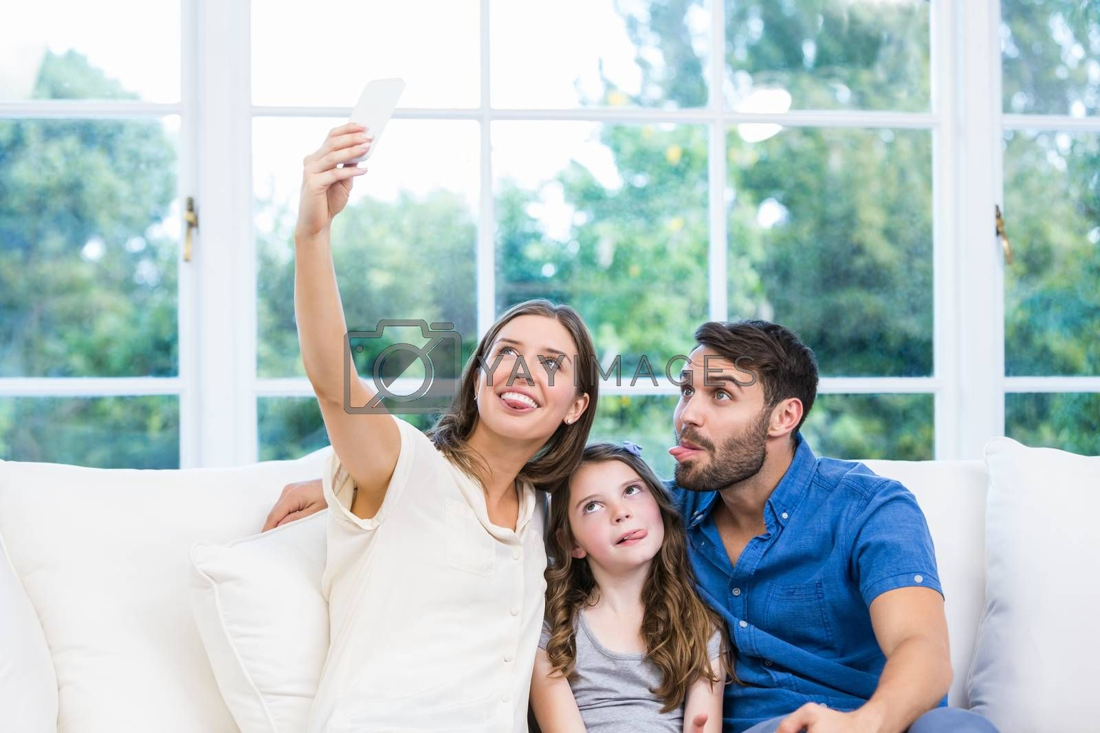 Woman clicking selfie with family on sofa  by Wavebreakmedia