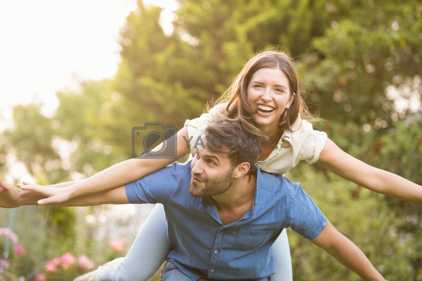 Happy man carrying woman on back at park