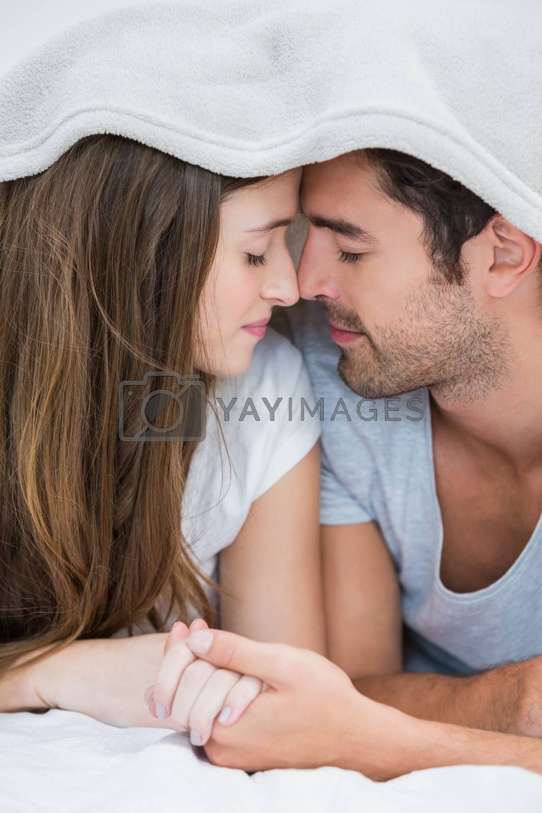 Close-up of couple romancing under blanket on bed at home