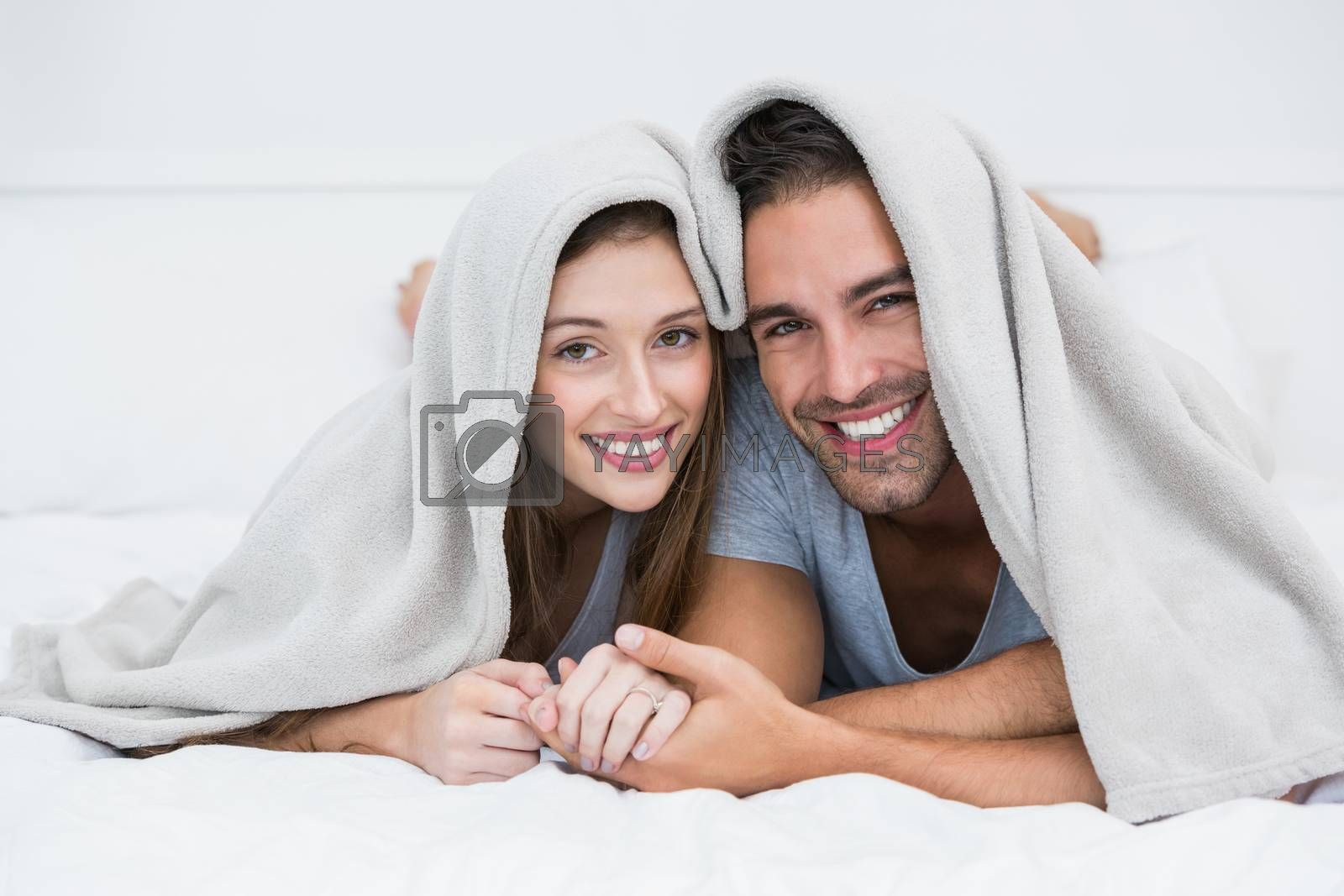 Portrait of happy couple lying under blanket on bed at home