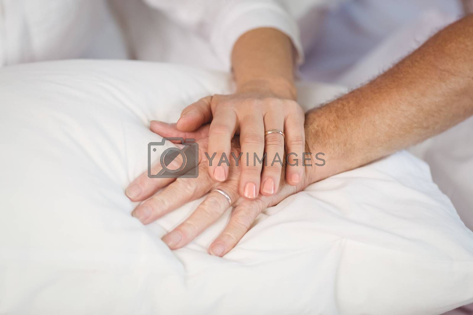 Cropped image of senior couple holding hands on pillow