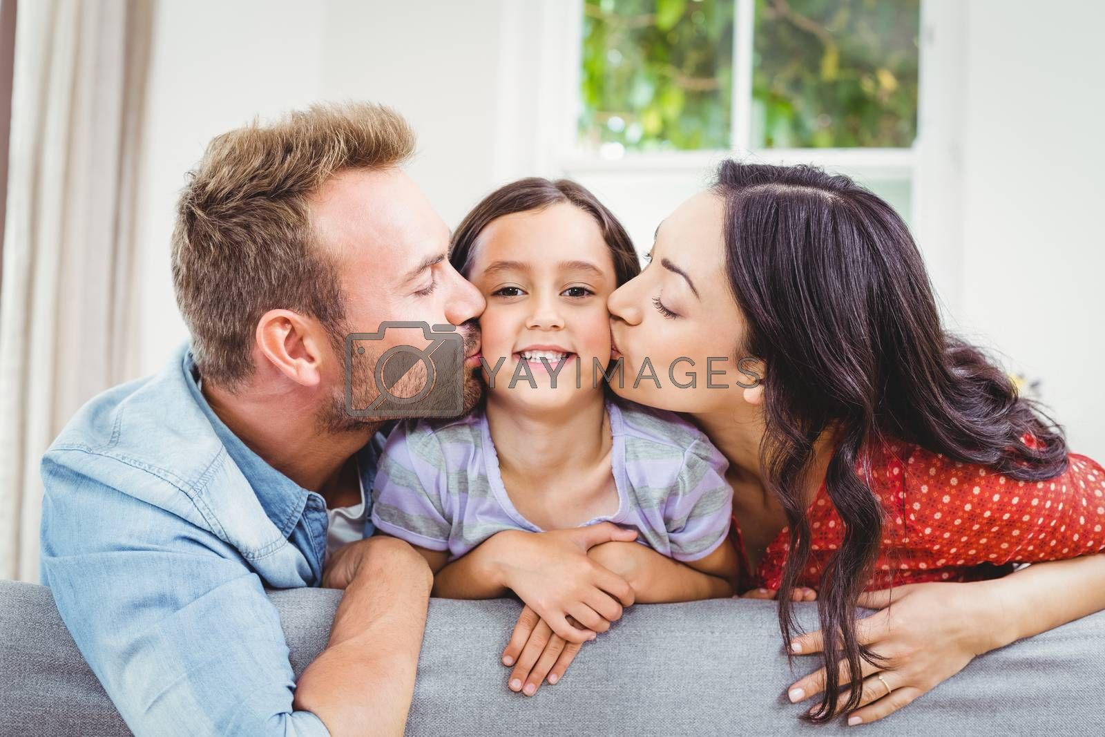 Mother and father kissing daughter at home  by Wavebreakmedia