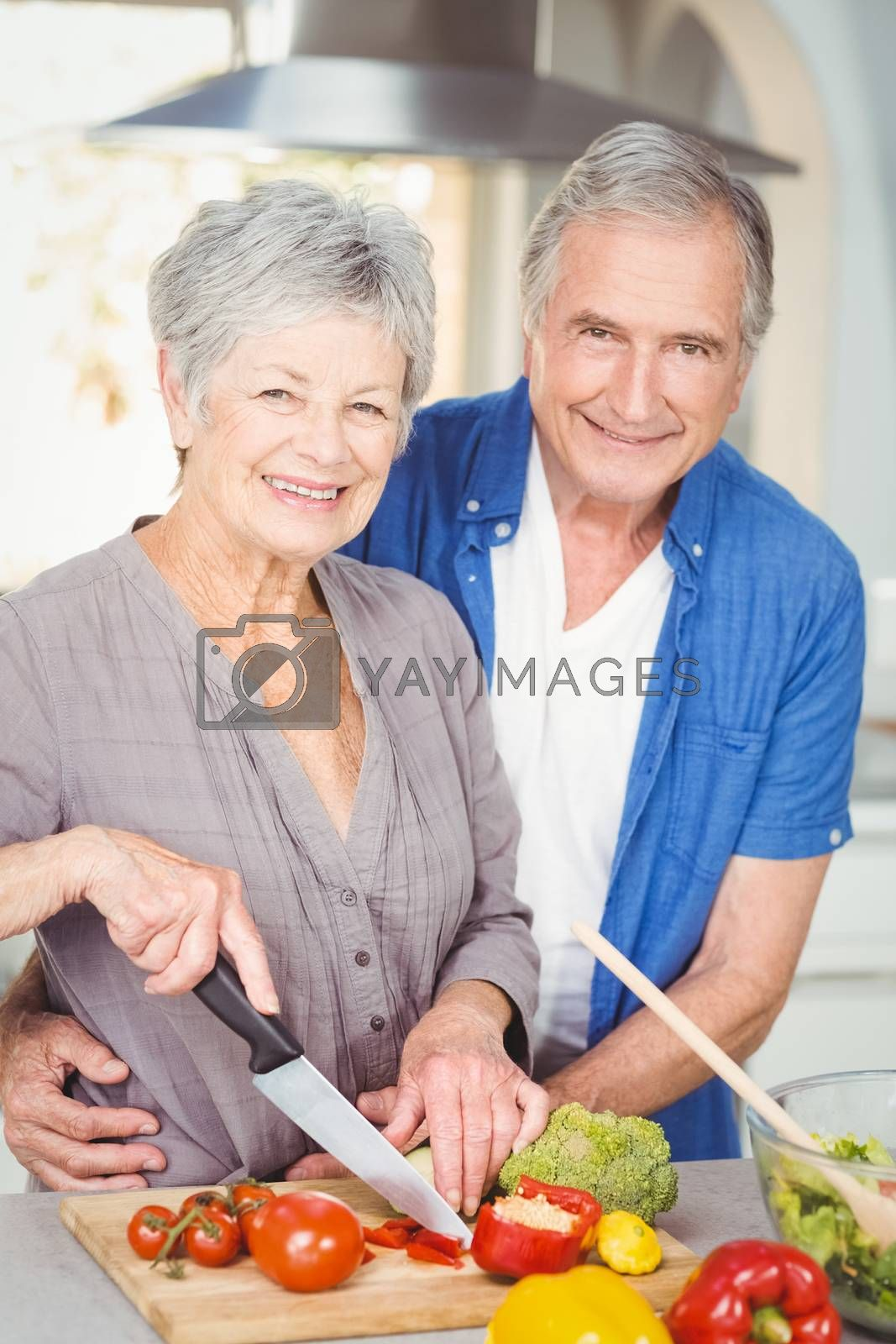 Portrait of senior woman cutting while man embracing in kitchen at home