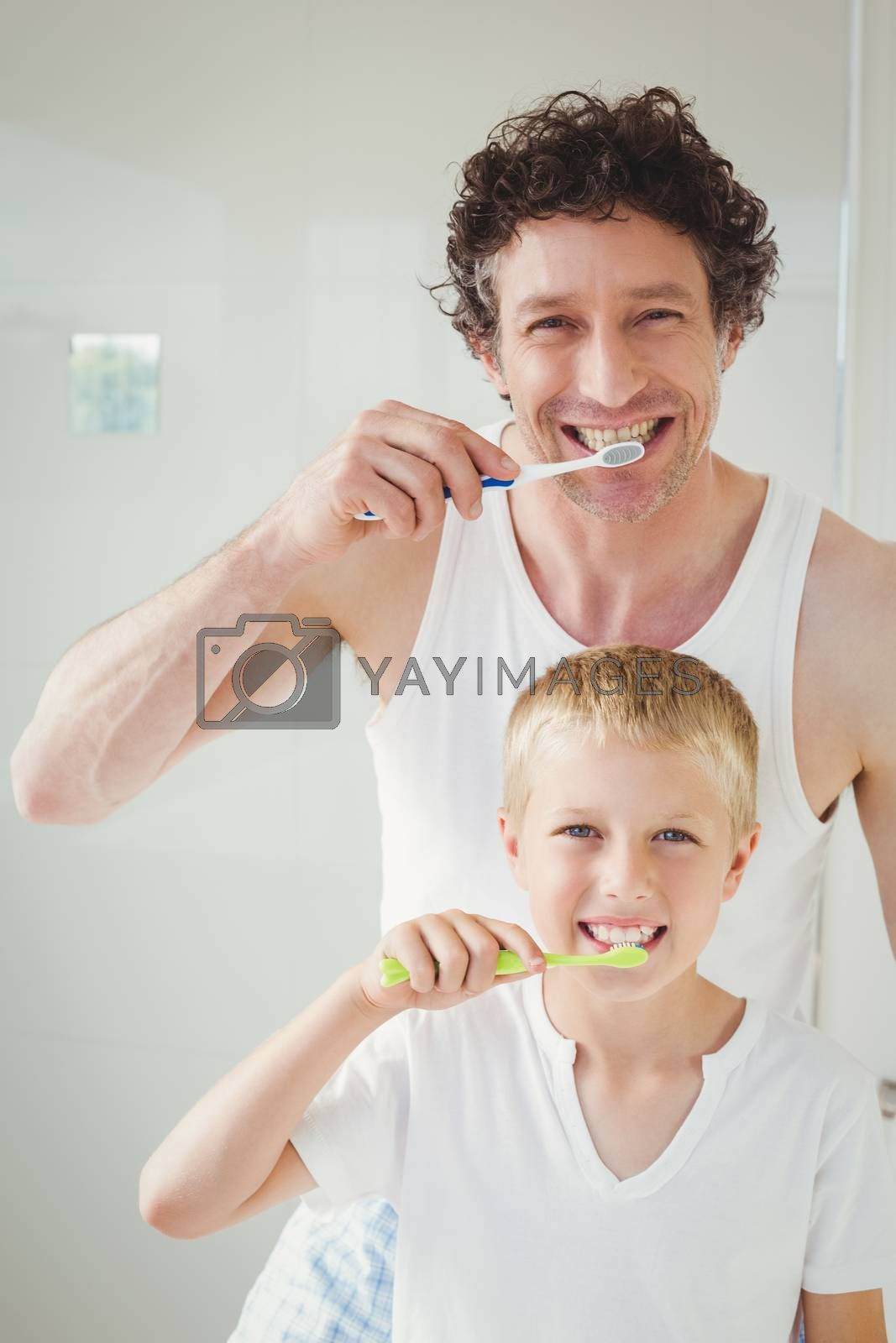 Portrait of father and son brushing teeth at home