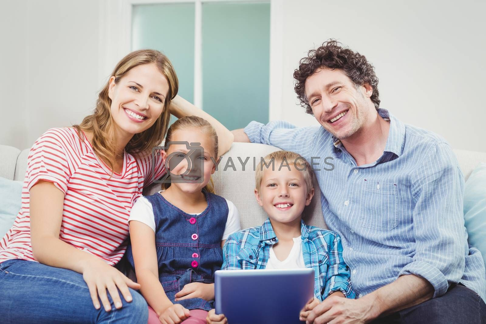 Happy family with digital tablet sitting on sofa by Wavebreakmedia