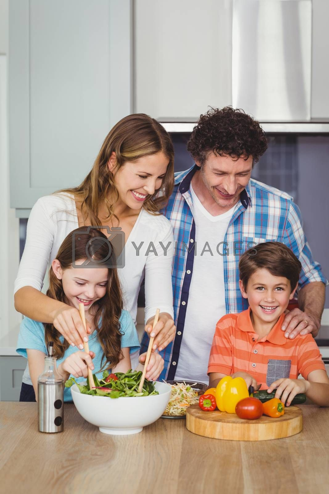 Happy family standing by table in kitchen by Wavebreakmedia