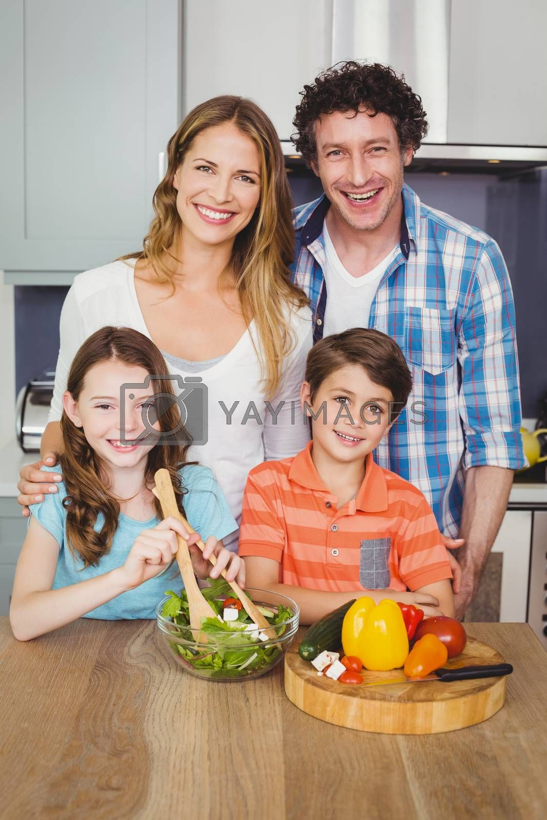 Portrait of happy family preparing vegetable salad in kitchen at home