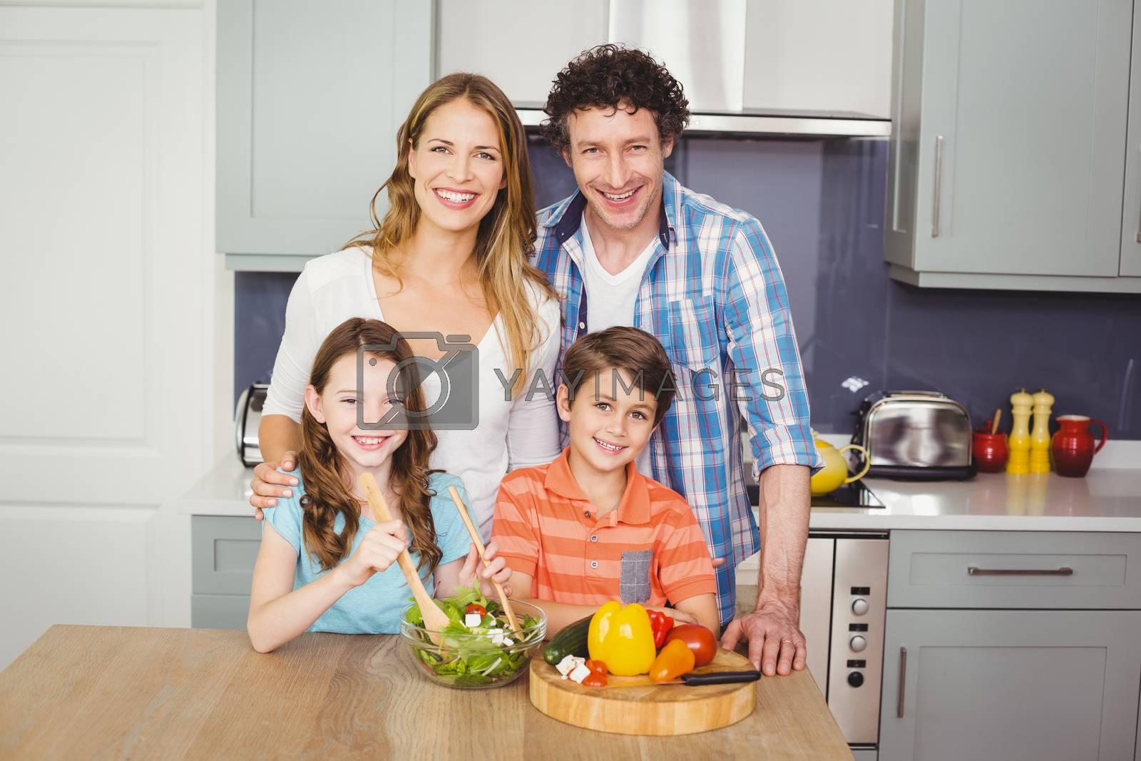 Portrait of smiling family preparing vegetable salad in kitchen
