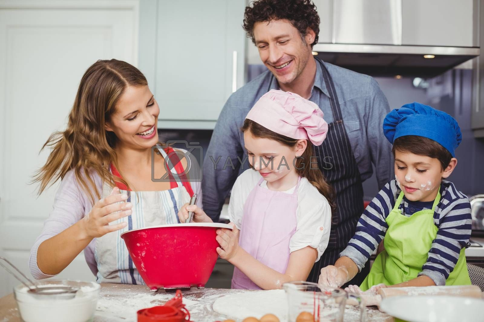 Happy family preparing food in kitchen by Wavebreakmedia