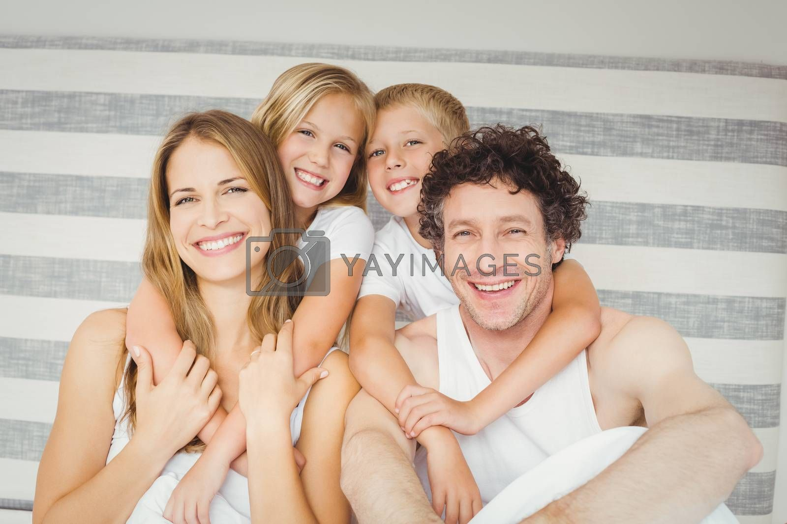 Portrait of joyful family on bed at home