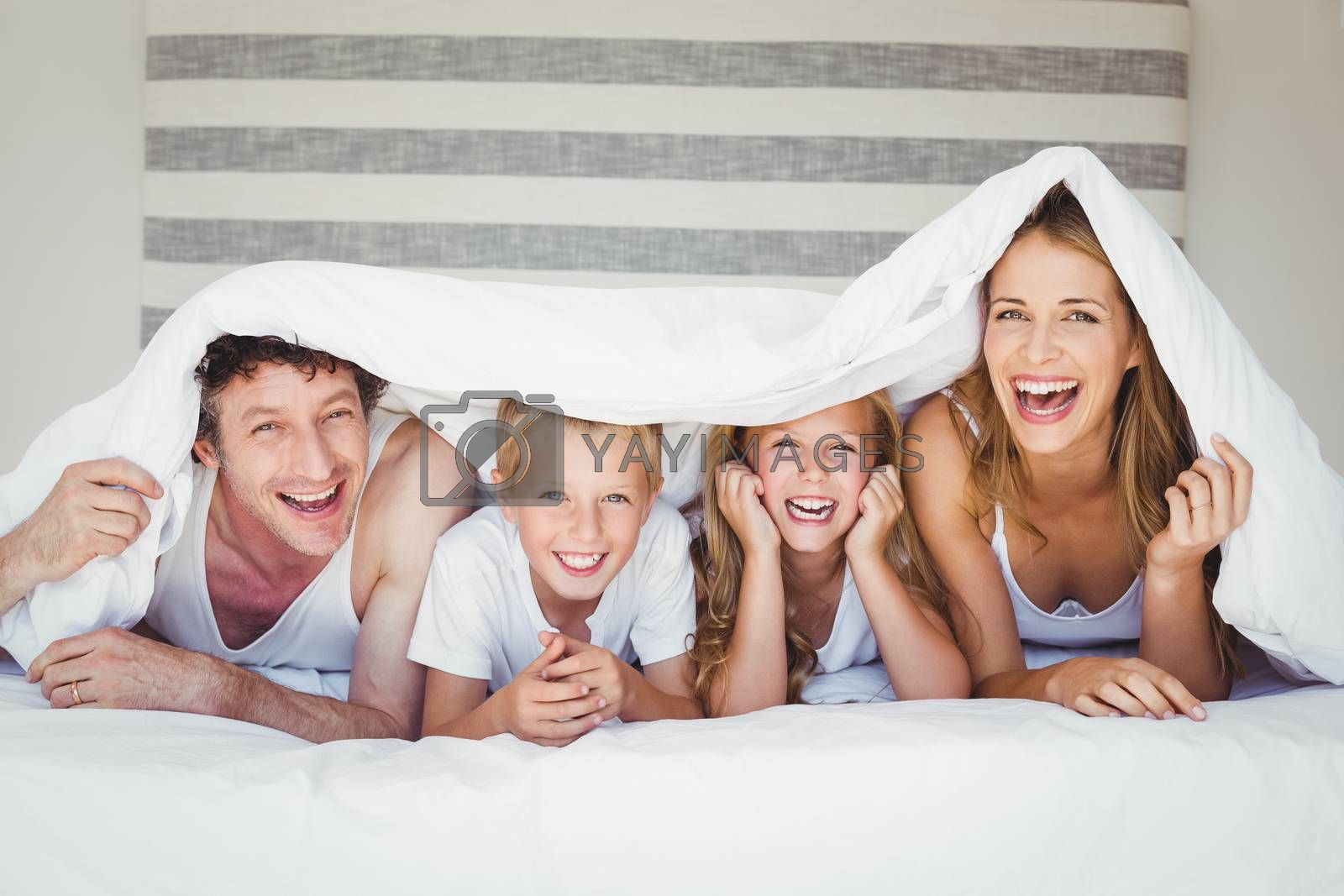 Portrait of smiling happy family covered with duvet on bed at home
