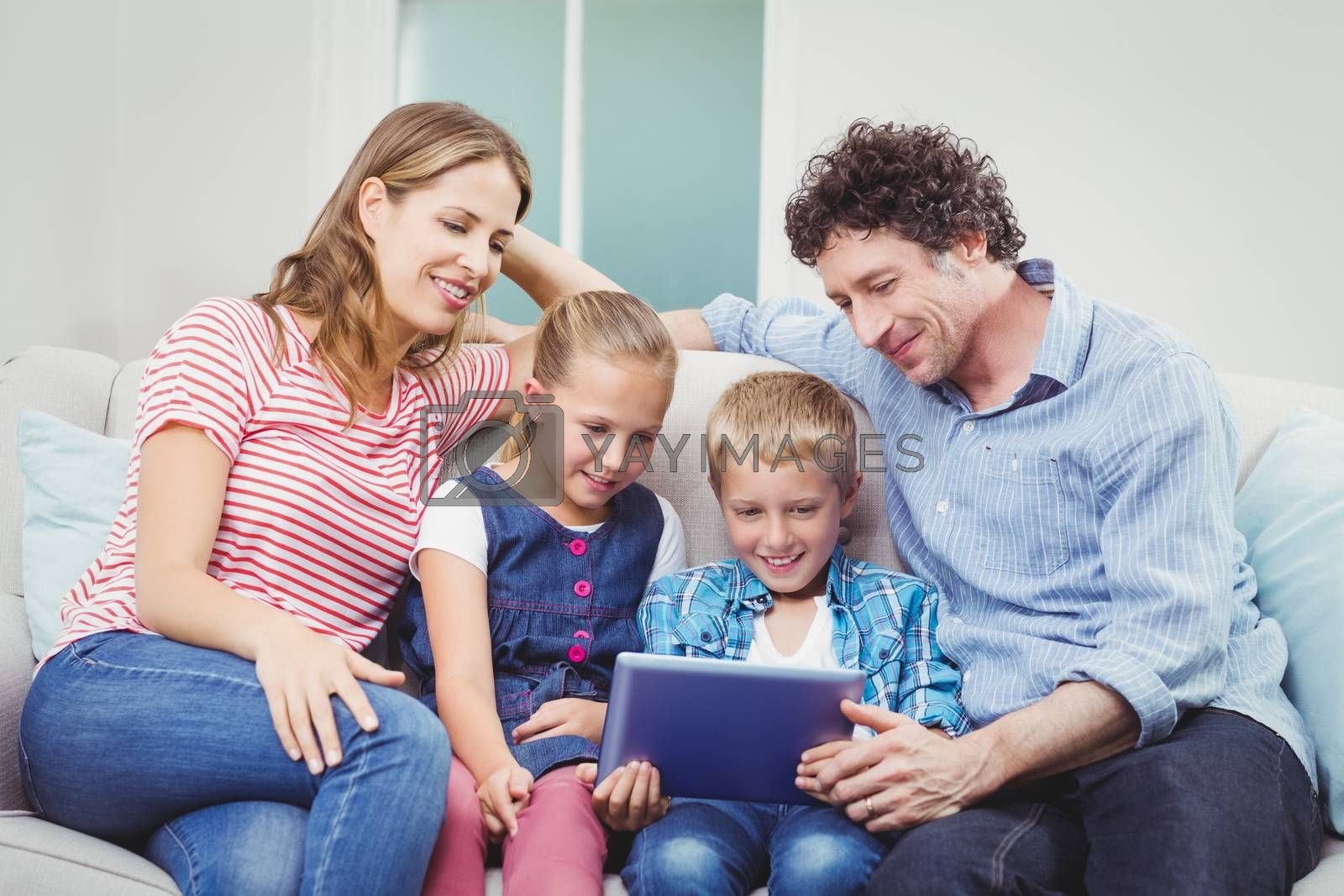 Family smiling and looking in digital tablet while sitting on sofa at home